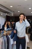 Terno formal considerável do desgaste de homem do negócio que guarda o revestimento nas mãos na loja moderna do Menswear fotos de stock royalty free
