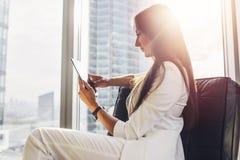 Terno vestindo da mulher bem sucedida que senta-se na poltrona usando o tablet pc em seu apartamento do sótão no centro da cidade fotografia de stock