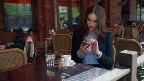 Terno vestindo da mulher de negócios atrativa usando Smartphone em um café exterior, café bebendo Movimento lento profissional vídeos de arquivo