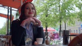 Terno vestindo da mulher de negócios atrativa usando Smartphone em um café exterior, café bebendo Movimento lento profissional video estoque