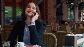 Terno vestindo da mulher de negócios atrativa usando Smartphone em um café exterior, café bebendo Movimento lento profissional filme