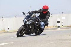 Terno vestindo da segurança do homem novo e anti equitação vermelha do capacete da batida Fotografia de Stock Royalty Free