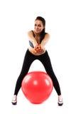 Terno vestindo do treinamento da menina magro com a bola do gym que oferece um tomate imagem de stock