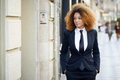 Terno vestindo e laço da mulher de negócios preta no fundo urbano fotografia de stock royalty free