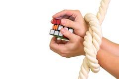 TERNOPIL, УКРАИНА, 27-ОЕ НОЯБРЯ 2018: Куб собирая Rubik с перевязанными руками с веревочкой стоковое изображение