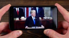 Ternopil Ukraina - Februari 19, 2018: ser USA presidenten Donald Trump på smartphonen arkivfilmer