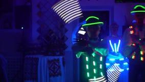 Ternopil Ukraina, mars 2019: Behagfulla grabbar och flickor som dansar i de glödande dräkterna Laser-show, ljus show stock video