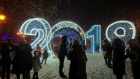 People are photographed near the big light garlands. Heavy snow fell royalty free stock photos