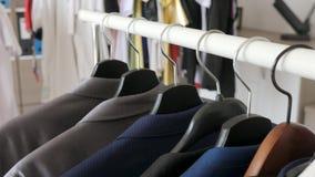 Ternos de negócio e camisas do negócio em ganchos em uma loja video estoque