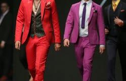 Ternos vermelhos da pista de decolagem do desfile de moda e cor-de-rosa bonitos Imagem de Stock Royalty Free