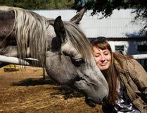 Ternura A menina pressionou sua cara ao cavalo Imagem de Stock