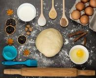 Terrón de la pasta, huevos y crema agria confeccionados, moldes que cuecen, en superficie de trabajo imágenes de archivo libres de regalías