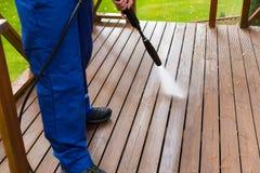 Terraço de madeira de limpeza com arruela de alta pressão imagens de stock royalty free