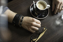 Terraço típico do café com o copo do coffe na tabela Mãos do `s do homem Fotografia de Stock Royalty Free