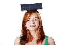 A terra arrendada adolescente de sorriso da menina registra em sua cabeça. Imagem de Stock