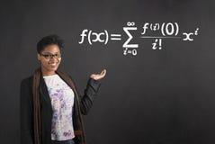 A terra arrendada africana da mulher distribui com equação matemática no fundo do quadro-negro fotos de stock royalty free
