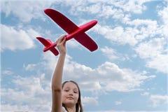 Terra arrendada bonita da criança nas mãos um avião vermelho do brinquedo em um fundo do céu azul imagens de stock