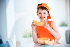 A terra arrendada bonito do rapaz pequeno cortou o melão alaranjado do cantalupo nas mãos Fotos de Stock