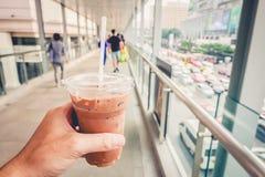 A terra arrendada congelou o Latte do café à disposição ao andar através da passagem superior na manhã imagens de stock