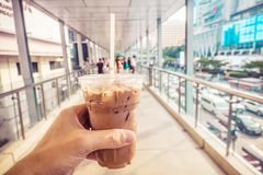 A terra arrendada congelou o Latte do café à disposição ao andar através da passagem superior na manhã imagem de stock royalty free