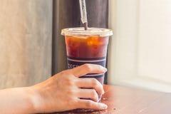 A terra arrendada da mão da mulher congelou o café no copo afastado Fotos de Stock Royalty Free