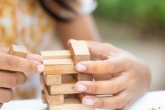 Terra arrendada da mão da menina que joga o bloco de madeira, imagem de stock