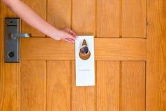 A terra arrendada da mão da mulher e pendura o quadro indicador não perturba na porta no hotel foto de stock royalty free