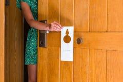 A terra arrendada da mão da mulher e pendura o quadro indicador não perturba na porta no hotel foto de stock