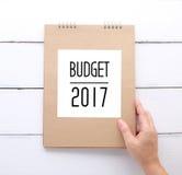 A terra arrendada da mão recicla o caderno de papel com palavra de 2017 orçamentos Imagens de Stock