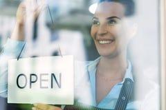 A terra arrendada da mulher aberta assina dentro o café Imagens de Stock