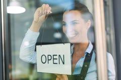 A terra arrendada da mulher aberta assina dentro o café Imagem de Stock