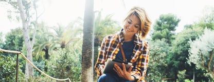 Terra arrendada da pessoa do moderno na tabuleta digital das mãos com tela, leitura do sorriso da moça no computador na palma do  imagens de stock royalty free