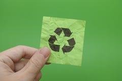 A terra arrendada da pessoa recicla o símbolo em sua mão Foto de Stock