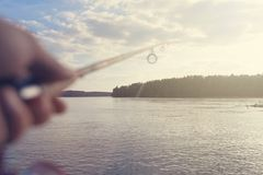 Terra arrendada da vara de pesca e da mão do carretel Profundidade de campo rasa foto de stock royalty free