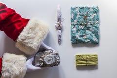 Terra arrendada de braços de Papai Noel diversos presentes foto de stock