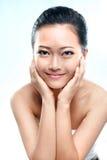 Terra arrendada de sorriso da mulher asiática sua cabeça imagem de stock royalty free