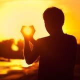 Terra arrendada do homem nas mãos o sol de ajuste fotografia de stock