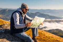 Terra arrendada do homem novo do moderno nas mãos e vista no mapa no fundo da montanha imagem de stock