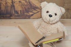 Terra arrendada e leitura do brinquedo do urso um livro Imagem de Stock Royalty Free