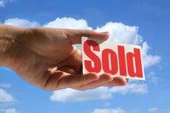 A terra arrendada fêmea da mão vendeu o cartão Fotografia de Stock Royalty Free