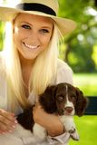 Terra arrendada fêmea de sorriso seu filhote de cachorro. Foto de Stock