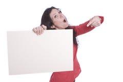 Terra arrendada fêmea surpreendida e apontar um cartão branco Fotografia de Stock