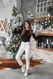 A terra arrendada feliz da mulher do sorriso entrega os balões de ano novo e o salto na sala decorada com árvore e chaminé de Nat imagens de stock royalty free