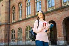 A terra arrendada feliz do estudante leva embora o copo de café fora imagens de stock