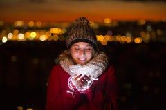A terra arrendada iluminated bonita da mulher conduziu a luz na noite de Natal Fotos de Stock