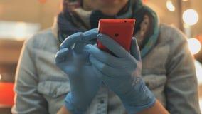 Terra arrendada mestra um vermelho do telefone em luvas de borracha azuis filme