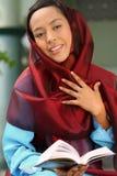 Terra arrendada muçulmana Qur'an da menina fotografia de stock