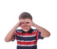 A terra arrendada pequena do modelo do menino entrega binóculos Fotos de Stock