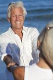 A terra arrendada sênior feliz da dança dos pares entrega a praia Fotos de Stock Royalty Free