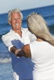 A terra arrendada sênior feliz da dança dos pares entrega a praia Fotografia de Stock Royalty Free